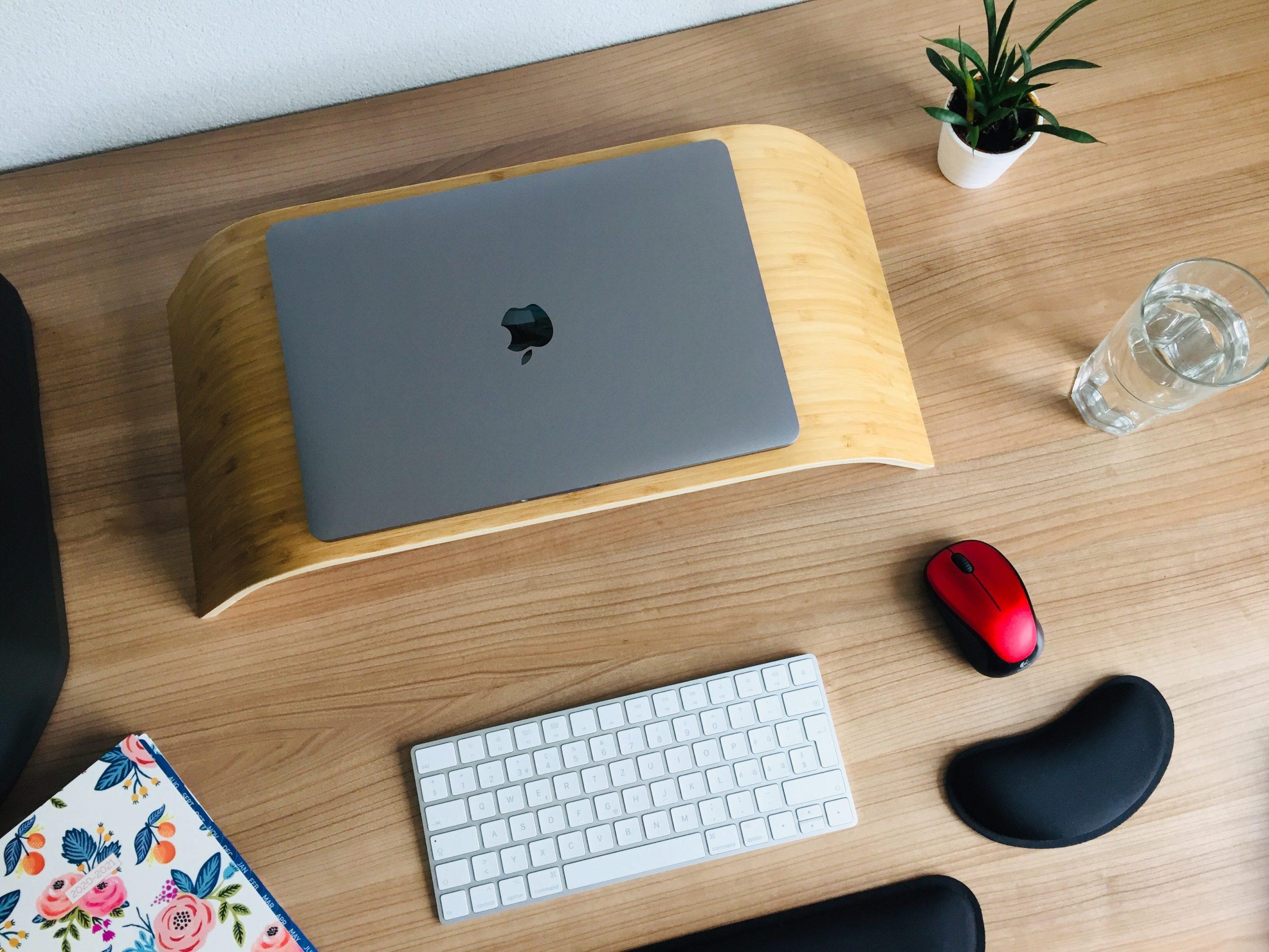 Ergonomischer Arbeitsplatz: Ein Laptop auf einer erhöhtem Bank. Davor Tastatur und Maus mit Handgelenks-Stützen.