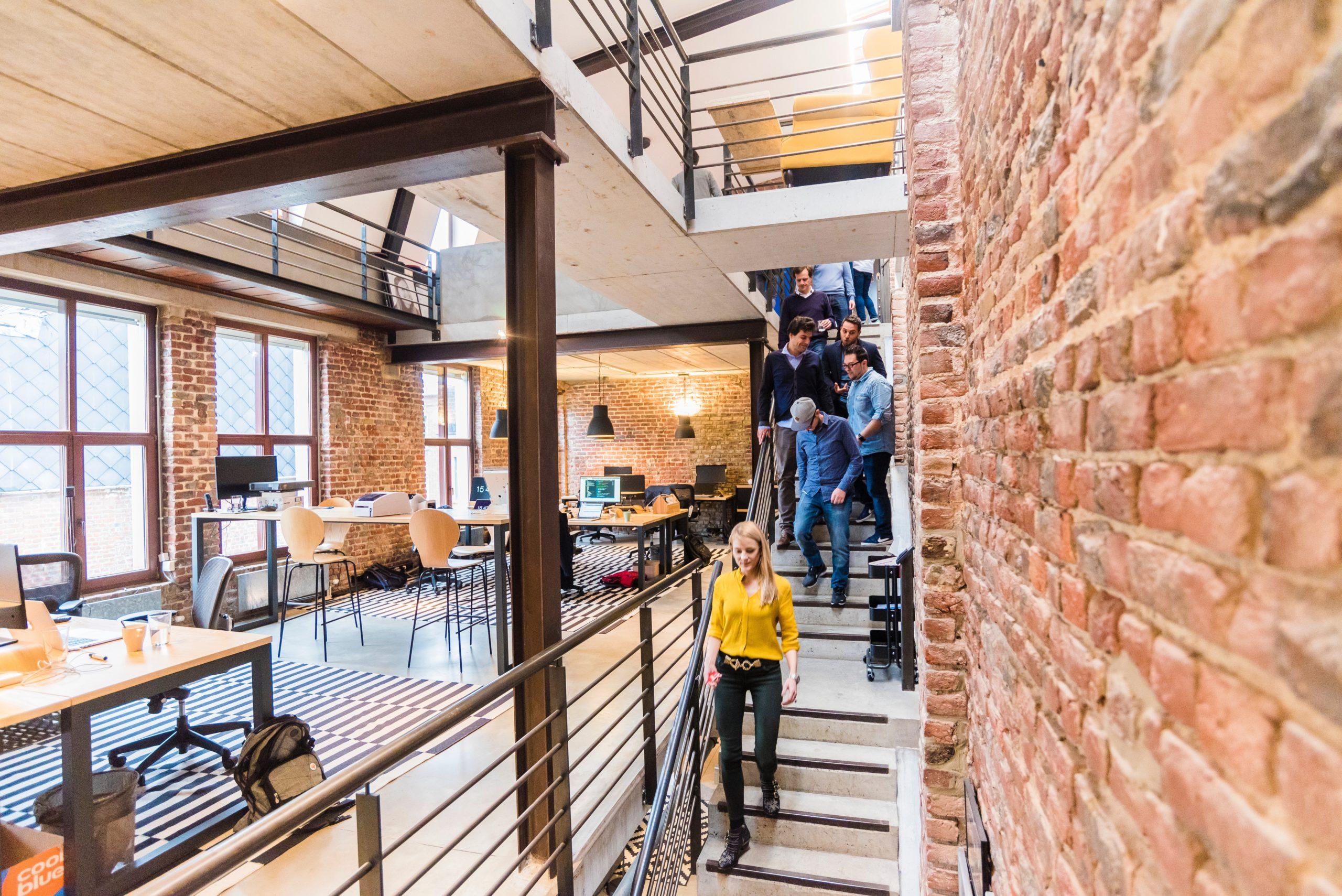 Angestellte gehen eine Treppe hinab. Links von Ihnen ist ein offener Büroraum zu erkennen.